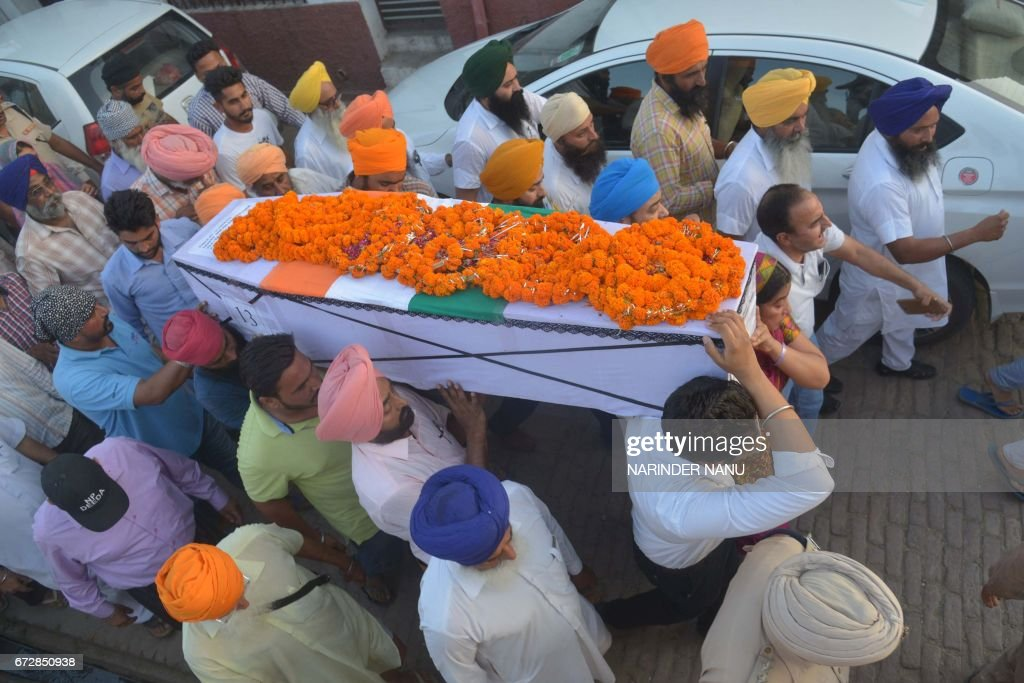 Baljit Kaur and her son Amritbir Singh carry the coffin of her husband Indian Central Reserve Police Force personnel Raghbir Singh at his funeral in..