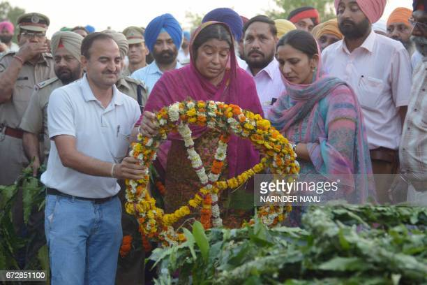 Baljit Kaur laying wreath on the pyre of her husband Indian Central Reserve Police Force personnel Raghbir Singh at his funeral in Sathiala village...