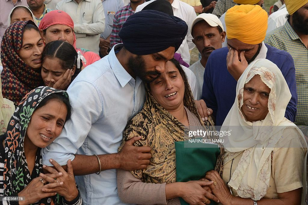 Baljit Kaur wife of Indian army soldier Satnam Singh cries with relatives during his cremation ceremony at Bhuse village some 30 km from Amritsar on..