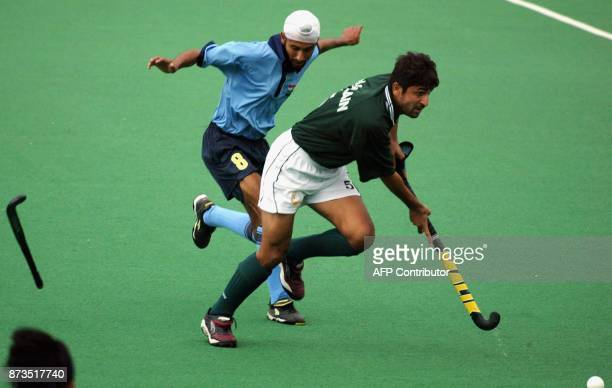 Baljit Singh Saini of India loses his stick as he chases Mohammad Saqlain of Pakistan during their match in the trinations tournament at Perth Hockey...