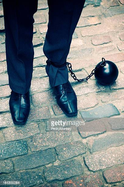 Ball and Chain Businessman Stands on Cobbled Street