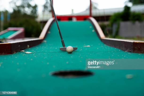 ball and club playing miniature golf - miniature golf stock photos and pictures