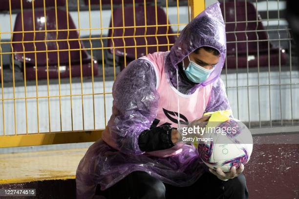 Ball boy cleans the ball with alcohol during a match between Saprissa and Limon FC as part of round 18 of Liga Promerica at Ricardo Sapirssa Stadium...