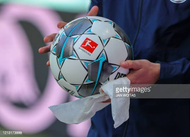 Ball boy disinfects a ball prior to the German first division Bundesliga football match RB Leipzig v SC Freiburg on May 16, 2020 in Leipzig, eastern...