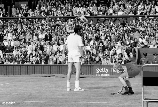 A ball boy gives Ilie Nastase back his racket after the Romanian had threw it away in disgust during his fourth round clash with Tom Okker of the...