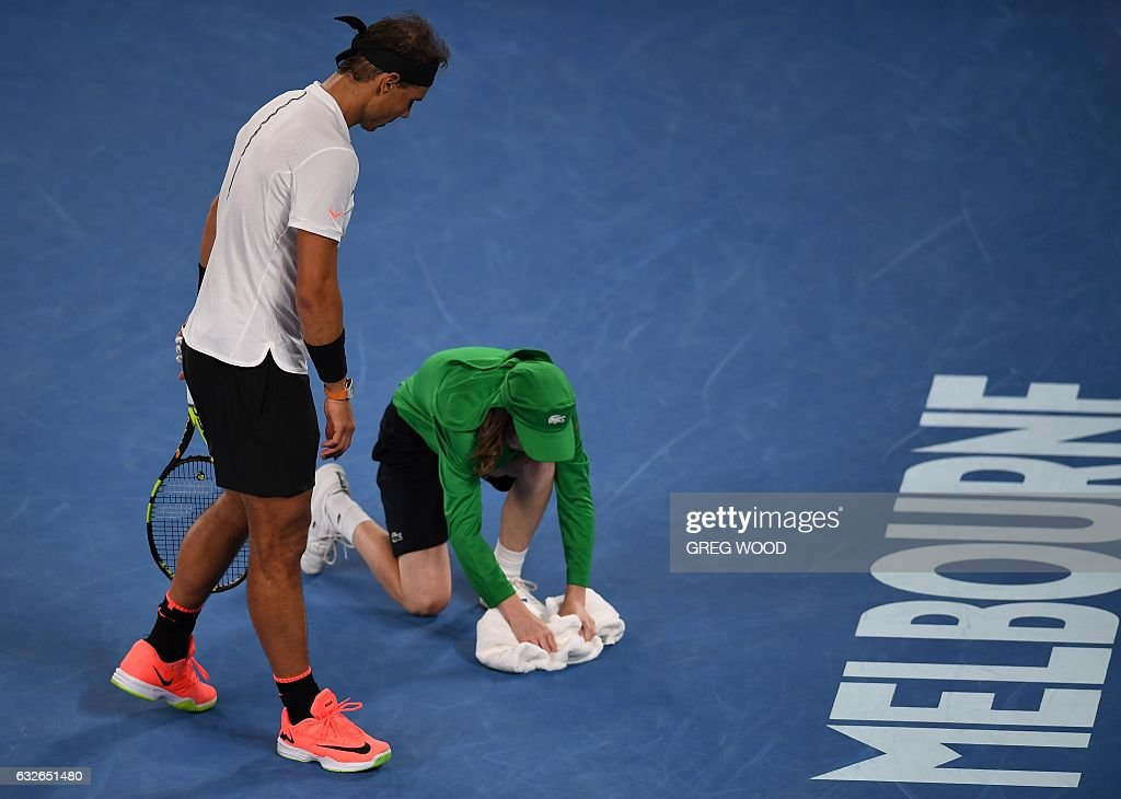 TOPSHOT - A ball boy is watched by Spain's Rafael Nadal in his game against Canada's Milos Raonic during their men's singles quarter-final match on day ten of the Australian Open tennis tournament in Melbourne on January 25, 2017. / AFP / GREG