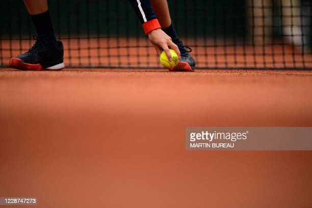 Ball boy picks up a ball during the women's singles first round tennis match between Slovakia's Anna Karolina Schmiedlova and Venus Williams of the...