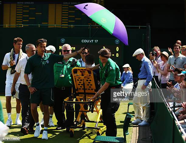 A ball boy receives medical attention after collapsing on court 17 during day three of the Wimbledon Lawn Tennis Championships at the All England...