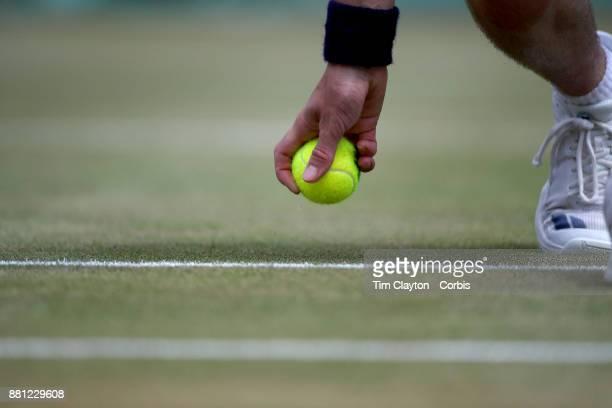 A ball boy retreives a tennis ball on a grass court during the Wimbledon Lawn Tennis Championships at the All England Lawn Tennis and Croquet Club at...