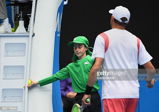 A ball boy retrieves a ball stuck in the umpire's chair as Bob Bryan of the US approaches as he and his partner Mike Bryan of the US play against...