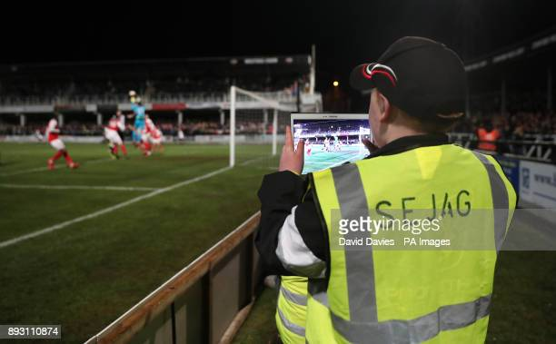 A Ball boy takes a photo on his tablet during the Emirates FA Cup Second Round Replay at Edgar Street Hereford
