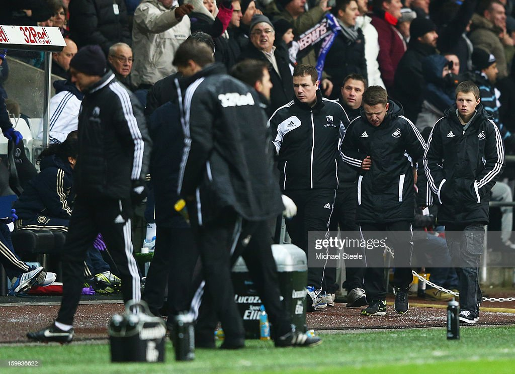 A ball boy (2R) walks off of the pitch after being kicked by Eden Hazard of Chelsea who is sent off during the Capital One Cup Semi-Final Second Leg match between Swansea City and Chelsea at Liberty Stadium on January 23, 2013 in Swansea, Wales.