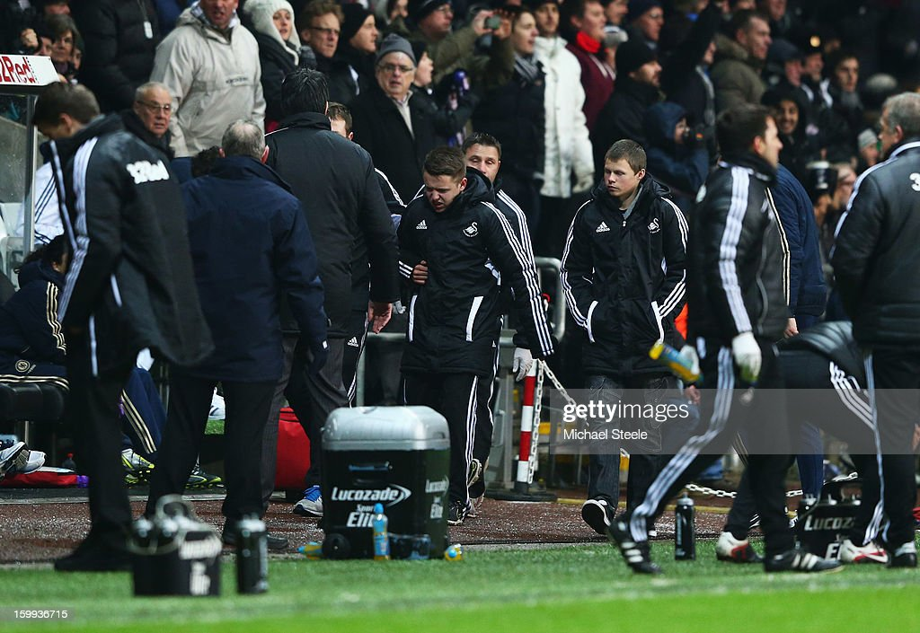 A ball boy (C) walks off of the pitch after being kicked by Eden Hazard of Chelsea who is sent off during the Capital One Cup Semi-Final Second Leg match between Swansea City and Chelsea at Liberty Stadium on January 23, 2013 in Swansea, Wales.