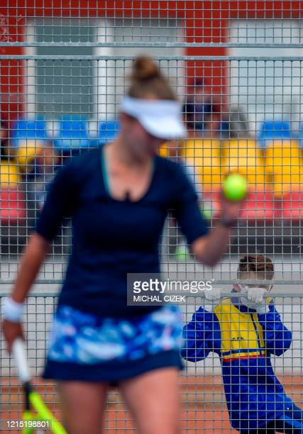 Ball boy wearing gloves and a face mask watches Czech Barbora Krejcikova playing against Czech tennis player Petra Kvitova during their match of the...