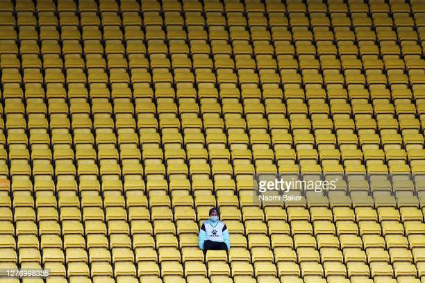 A ball boy/girl sits in the empty spectator stands during the Sky Bet Championship match between Watford and Luton Town at Vicarage Road on September...