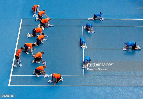 Ball boys and officials wipe water off Rod Laver Arena before the start of the men's doubles match between Jonathan Erlich and Andy Ram of Israel and...
