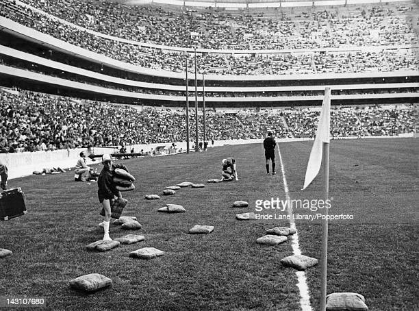 Ball boys collecting cushions thrown by irate fans at the Olympic soccer final between Hungary and Bulgaria at the Azteca Stadium Mexico City 26th...
