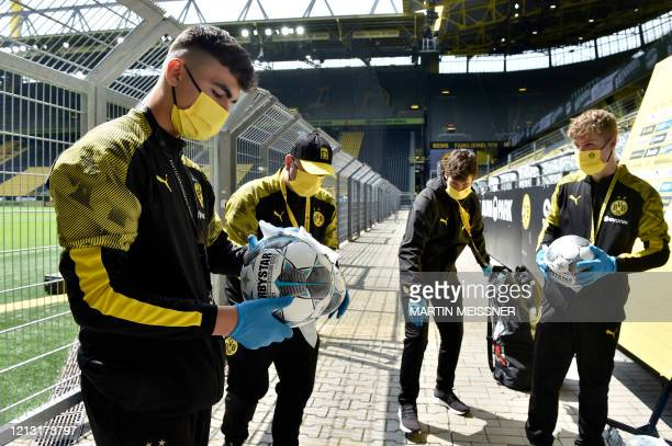 Ball boys disinfect the footballs prior to the German first division Bundesliga football match BVB Borussia Dortmund v Schalke 04 on May 16 2020 in...