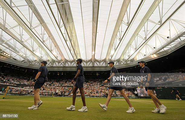 Ball boys enter Centre Court where the roof has been closed before the resumption of play between France's Amelie Mauresmo and Russia's Dinara Safina...