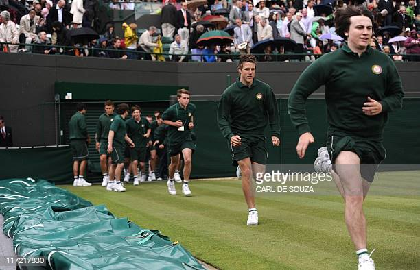 Ball boys run as the game between Spanish player Rafael Nadal and Luxembourg player Gilles Muller is interupted due to rain during the men's single...