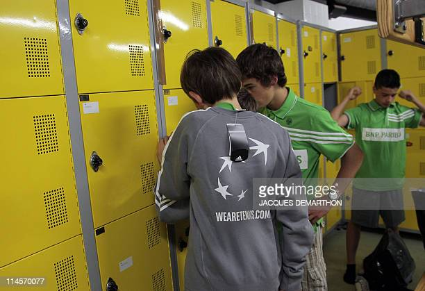 Ball boys try the official shirts in a changing room on May 14 2011 at RolandGarros stadium in Paris they will wear during the French Tennis Open...