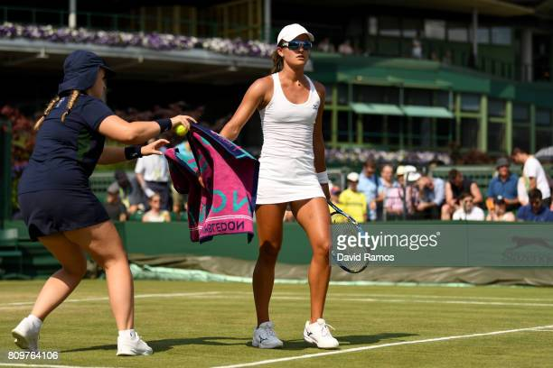 A ball girl collects a towel from Arina Rodionova of Australia plays a backhand during the Ladies Singles second round match against Zarina Diyas of...
