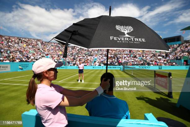 A ball girl holds an umbrella over the head of Christian Garin of Chile during a break in play during the First Round Singles Match between Christian...