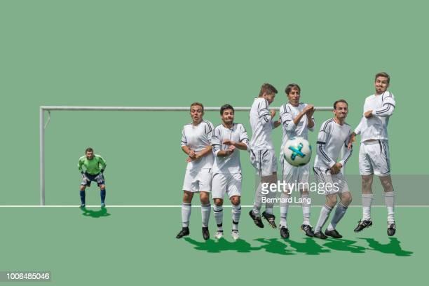 ball heading to defensive wall - verdediger voetballer stockfoto's en -beelden