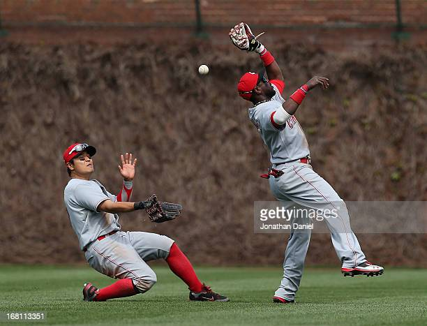 A ball hit by Alfonso Soriano of the Chicago Cubs falls between ShinSoo Choo and Brandon Phillips of the Cincinnati Reds at Wrigley Field on May 5...