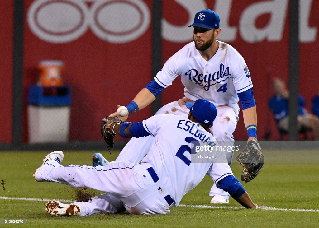 A ball hit by Jason Castro #21 of the Minnesota Twins drops fair between Alcides Escobar #2 and Alex Gordon #4 of the Kansas City Royals in the ninth inning at Kauffman Stadium on September 7, 2017 in Kansas City, Missouri.