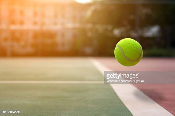 ball in mid-air at tennis court - tennis ball stock pictures, royalty-free photos & images