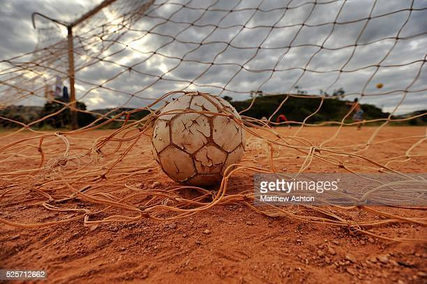 Ball in the back of a rustic goal net on a dust football pitch situated in between Rua Coronel Manuel Assuncao, Belo Horizonte and highway Rodovia...