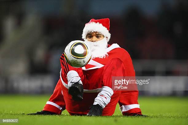 A ball juggler dressed as Father Christmas displays his skills at half time during the Barclays Premier League match between West Ham United and...