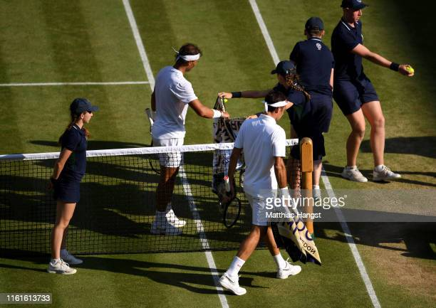 Ball kid passes a towel to Rafael Nadal of Spain as he and Roger Federer of Switzerland walk back to their chairs before a change of serve in their...