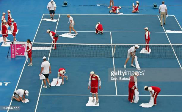 Ball kids dry the court with towels after rain stopped play during the match between Samantha Stosur of Australia and Flavia Pennetta of Italy during...