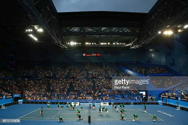 Ball kids dry the court with towels following a brief rain shower during the women's singles match between Daria Gavrilova of Australia and Coco...