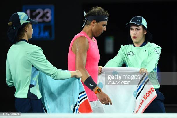 Ball kids give towels to Spain's Rafael Nadal during a break in his men's singles quarterfinal match against Austria's Dominic Thiem on day ten of...