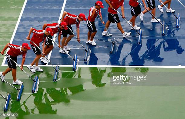Ball kids squeegee Center Court after a rain storm during Day 1 of the Western Southern Financial Group Women's Open on August 10 2009 at the Lindner...