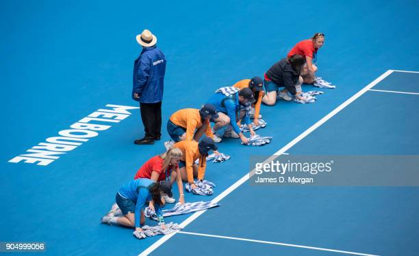 Ball kids use towels to clean the rain off the court for the match between Venus Williams of the USA and Belinda Bencic of Switzerland on day one of...