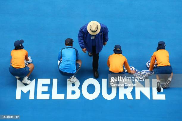 Ball kids wipe the surface of centre court with towels after rain fell on day one of the 2018 Australian Open at Melbourne Park on January 15 2018 in...