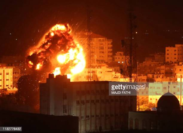 A ball of fire billows above buildings in Gaza City during reported Israeli strikes on March 25 2019 Israel's military launched strikes on Hamas...