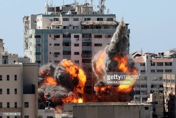 Ball of fire erupts from the Jala Tower as it is destroyed in an Israeli airstrike in Gaza city controlled by the Palestinian Hamas movement, on May...