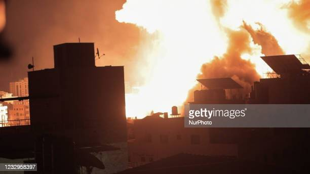 Ball of fire explodes above buildings in Gaza City as Israeli forces shell the Palestinian enclave, early on May 18, 2021. - Israeli jets kept up a...