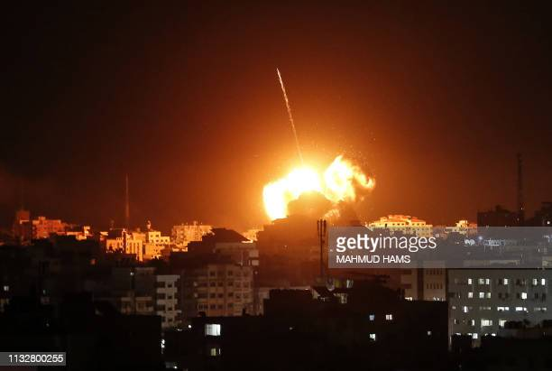 TOPSHOT A ball of fire lights the sky above a building believed to house the offices of Hamas chief in Gaza Ismail Haniyeh during Israeli strikes on...