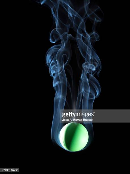 Ball of fire with a stela of smoke that falls down down on a black background. Spain