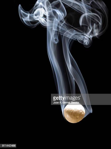 ball of fire with a stela of smoke that falls down down on a black background. spain - colour and abstract and impact not people stock photos and pictures
