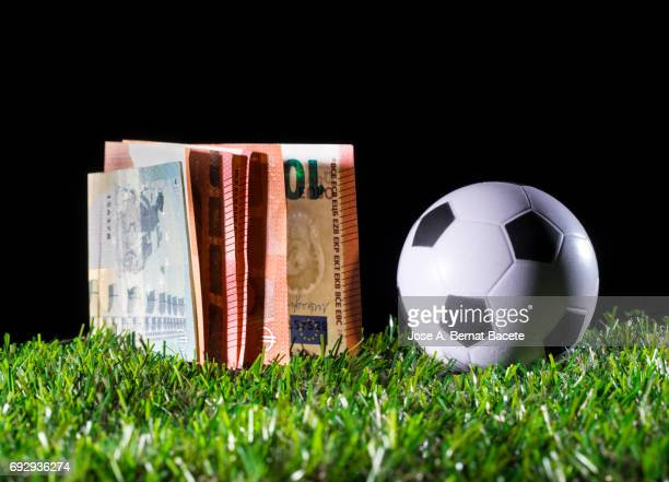 Ball of football on the lawn and a heap of tickets of Euro, business concept in the football