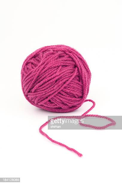 Ball of pink yarn on a white background