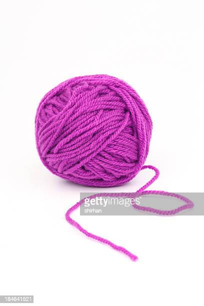 Ball of purple wool on a white background