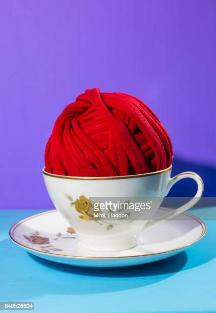 Ball of Red Yarn in Teacup on Blue Background